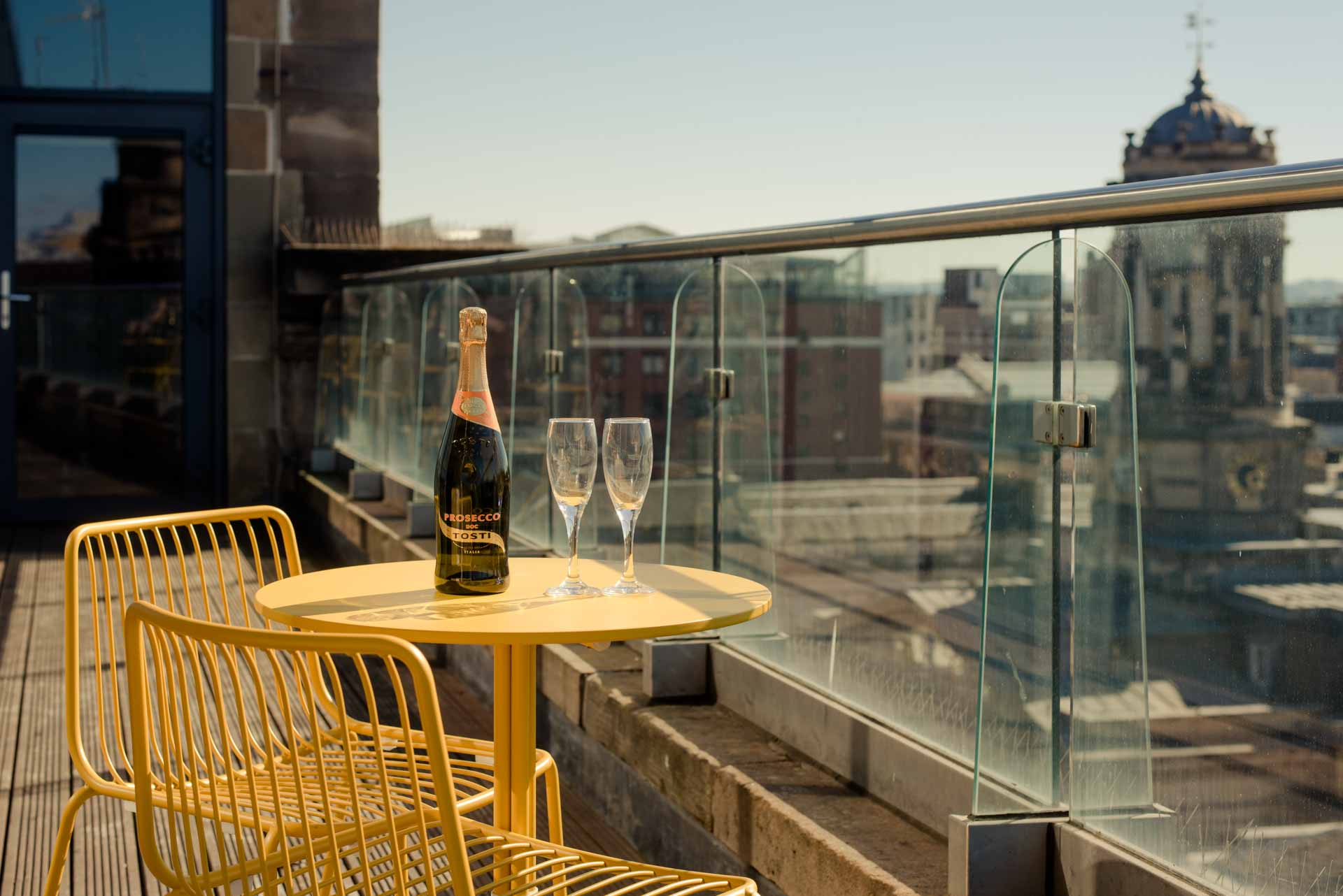 Table with Prosecco and glasses on the balcony of PREMIER SUITES PLUS Glasgow George Square